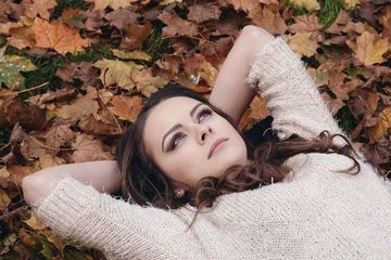 Girl laying on leaves, thinking