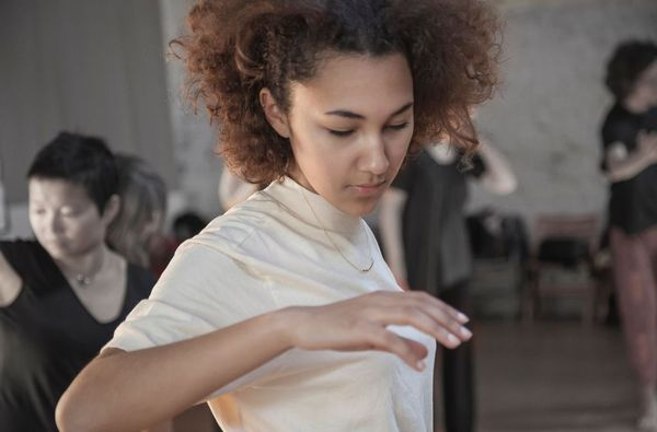 A young black woman moves her arm and shoulder girdle.